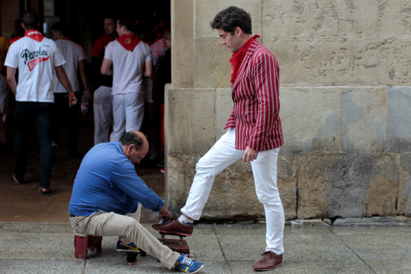 Alexander Fiske-Harrison having his shoes polished after running the bulls (Copyright Jim Hollander 2014)